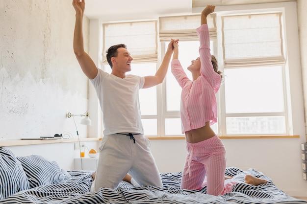 Jong mooi paar met plezier op bed in de ochtend blijven samen alleen thuis