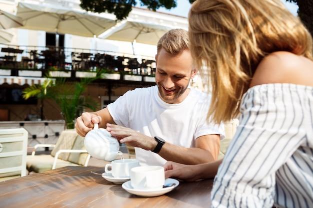 Jong mooi paar spreken, glimlachen, die in koffie rusten.