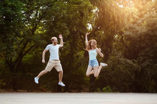 Jong mooi paar springen, glimlachen, vreugde, wandelen in het park.