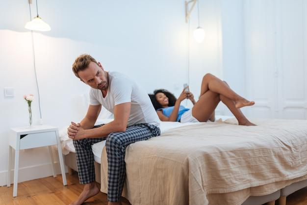 Jong mooi paar tussen verschillende rassen in bed dat met ontrouwproblemen wordt benadrukt