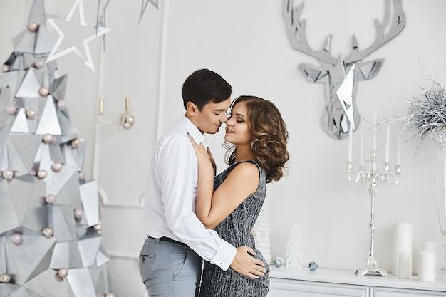 Jong mooi paar verliefd knuffelen in interieur met moderne stijlvolle decoratie voor kerstmis