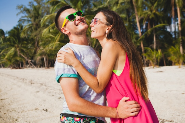 Jong mooi paar wandelen op tropisch strand, thailand, knuffelen, lachen, zonnebril, plezier hebben, hipster outfit, casual stijl, honingmaan, vakantie, zomer, zonnig, romantische stemming