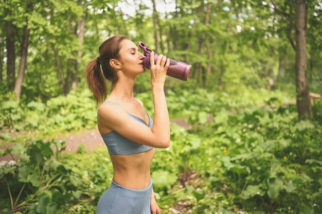 Jong mooi slim fit meisje in blauw sportkleding drinkwater uit een fles sport en fitness in de zomer park buiten doen
