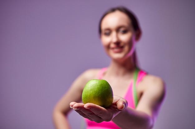 Jong mooi sportenmeisje in beenkappen en een bovenkant met een meetlint om zijn hals die een groene appel houdt. gezonde levensstijl.