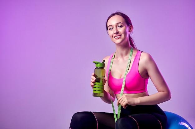 Jong mooi sportenmeisje in beenkappen en een bovenkant met een meetlint om zijn hals die waterfles houdt. gezonde levensstijl.
