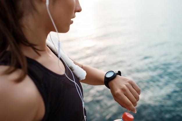 Jong mooi sportief meisje dat horloge tijdens zonsopgang over kust bekijkt.
