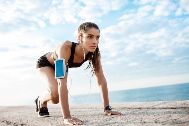 Jong mooi sportief meisje dat voorbereidingen treft over kust te lopen.