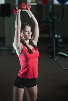 Jong, mooi, sportief meisje doet oefeningen met halters in de handen van de sportschool.