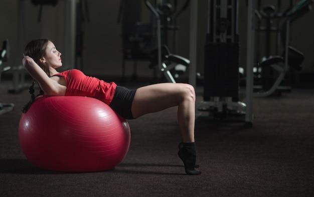 Jong, mooi, sportief meisje doet oefeningen op een fitball in de sportschool Premium Foto