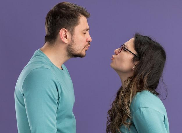 Jong mooi stel in blauwe vrijetijdskleding, man en vrouw die gelukkig verliefd gaan zoenen over een paarse muur