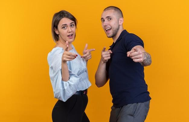 Jong mooi stel in vrijetijdskleding man en vrouw blij en positief wijzend met wijsvingers glimlachend staand