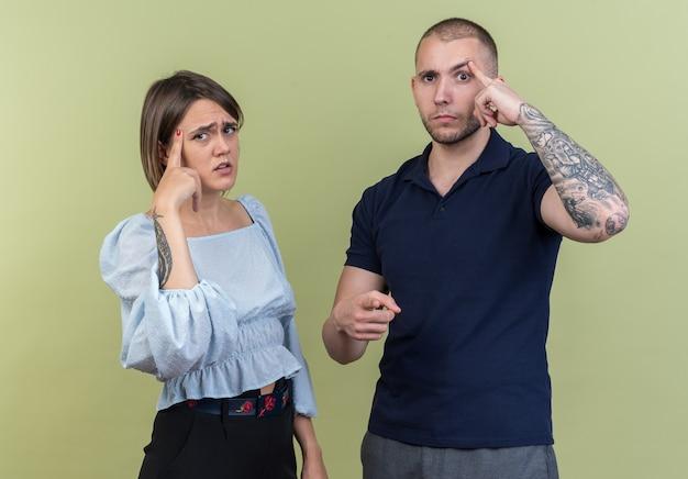 Jong mooi stel in vrijetijdskleding, man en vrouw die verward kijken, wijzend met wijsvingers naar tempels die staan