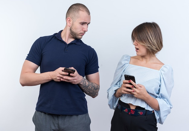 Jong mooi stel in vrijetijdskleding, man en vrouw met smartphones die verward naar elkaar kijken terwijl ze over een witte muur staan
