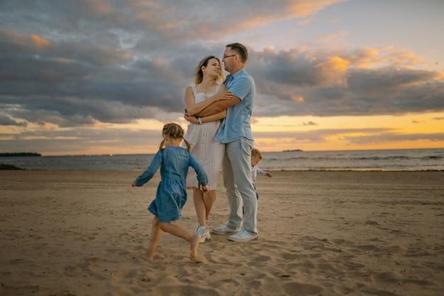 Jong mooi stel met rennende kinderen op het strand prachtige avondrood op de achtergrond
