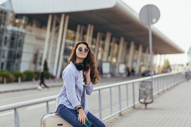 Jong mooi studentenmeisje dat op een taxiauto wacht, en aan muziek luistert
