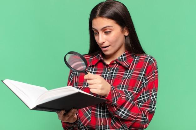 Jong mooi tienermeisje. geschokte of verbaasde uitdrukking. zoeken in een boekconcept