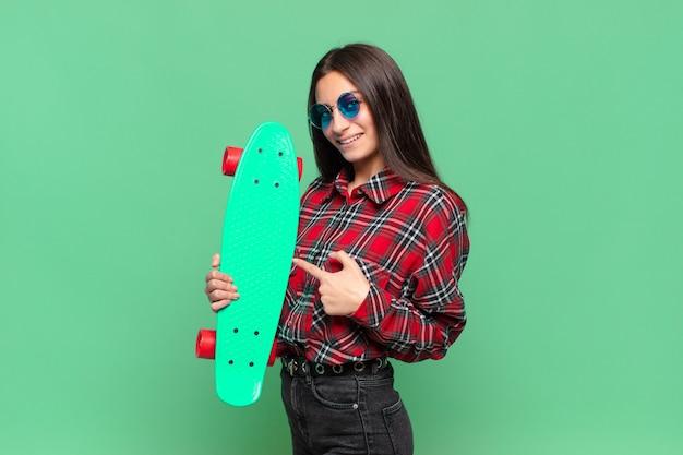 Jong mooi tienermeisje. wijzend gebaar. skate board concept