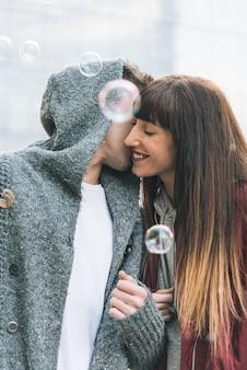 Jong mooi verliefd paar knuffelen elkaar midden op straat op een romantische manier met zeepbellen