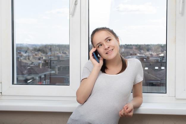 Jong, mooi, vrolijk meisje praten aan de telefoon met ouders, vriendin, vriendje, verheugt zich