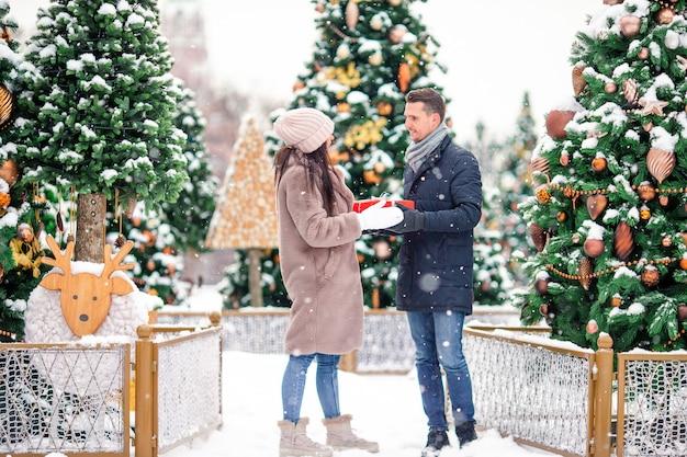 Jong mooi vrolijk paar het vieren kerstmis in de stadsstraat en het geven van gift aan elkaar.