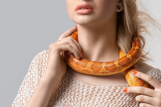 Jong, mooi, vrouw met slang om haar nek op grijs.