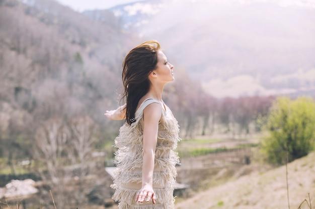 Jong mooi vrouwelijk model in een landschap met bergen en dorp, staande op een heuvel