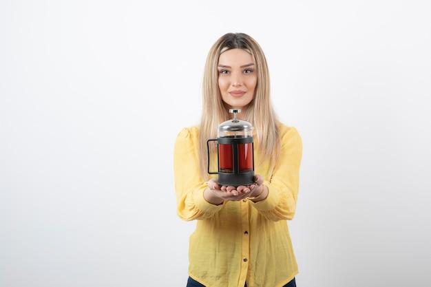 Jong mooi vrouwenmodel dat een theepot houdt.