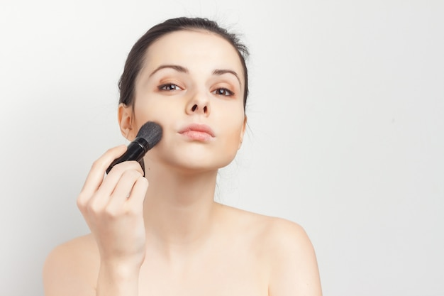 Jong mooi vrouwenportret dat make-upborstel doet