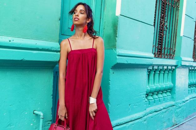 Jong mooi vrouwenportret die rode kleding dragen tegen groene muur in havana, cuba.