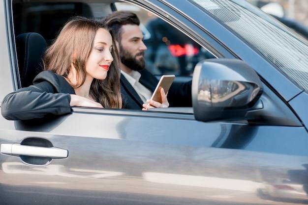 Jong mooi zakenpaar dat een auto in de stad bestuurt