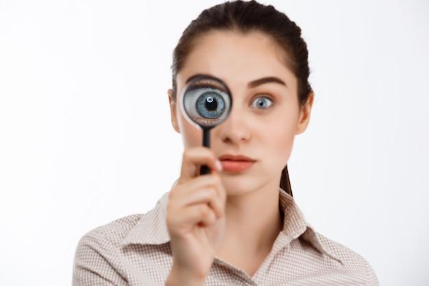 Jong mooi zeker donkerbruin meisje dat camera door meer magnifier over witte muur bekijkt.