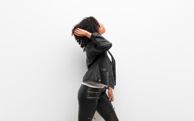 Jong mooi zwarte die een leerjasje dragen tegen witte muur