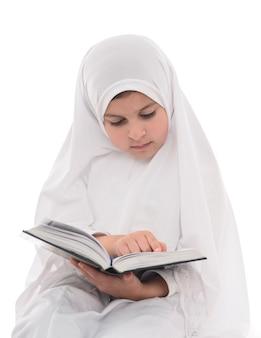 Jong moslimmeisje dat koran leest