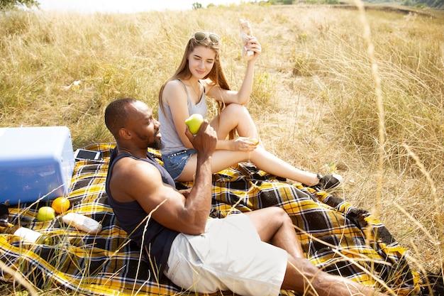 Jong multi-etnisch internationaal romantisch koppel buiten op de weide in zonnige zomerdag. afro-amerikaanse man en blanke vrouw met picknick samen. concept van relatie, zomer.