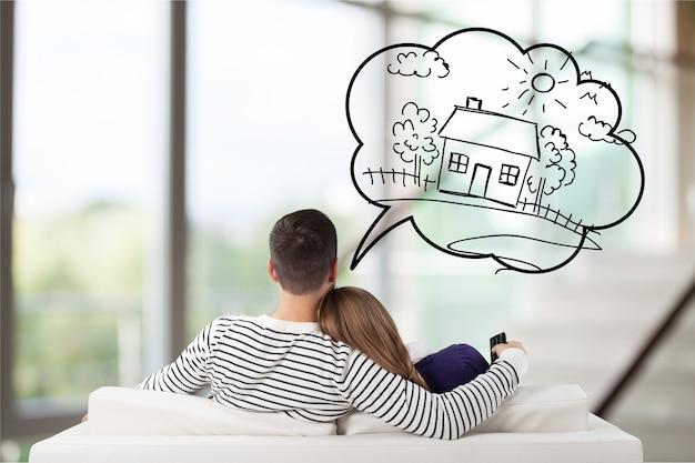 Jong nadenkend koppel zittend op de bank denkend aan het krijgen van hun eigen huis