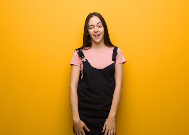 Jong natuurlijk mooi meisje knipogen, grappig, vriendelijk en zorgeloos gebaar