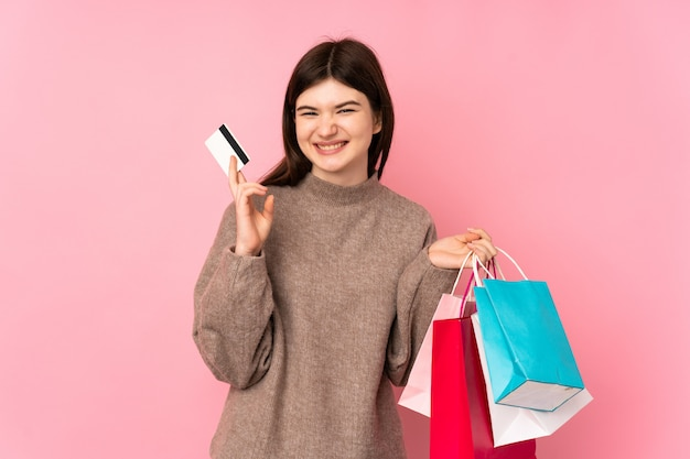 Jong oekraïens tienermeisje over roze muur met boodschappentassen en een creditcard