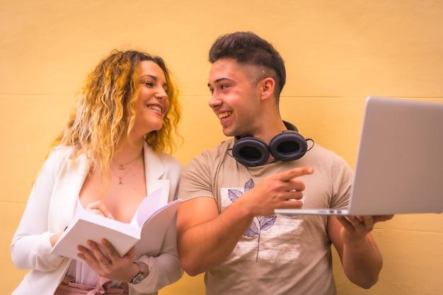 Jong ondernemerspaar dat groepswerk doet. met een gele achtergrond en met een computer, een jongen met muziekkoptelefoons en een meisje in een wit pak