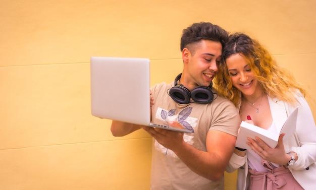Jong ondernemerspaar dat groepswerk met een computer doet. met een gele achtergrond, jongen in muziekhoofdtelefoons en meisje in wit kostuum