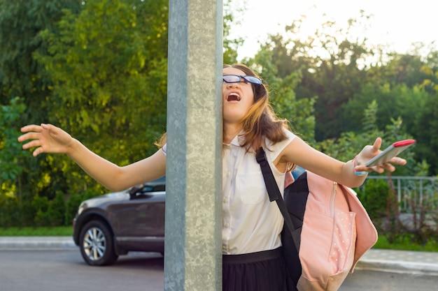 Jong onoplettend meisje, afgeleid door mobiele telefoon