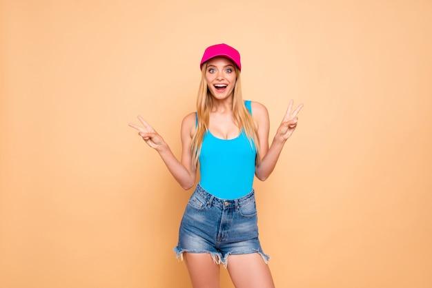 Jong opgewonden meisje dat de toevallige borrels van het jeansdenim, roze glb draagt en dubbel v-teken toont