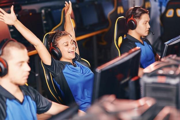 Jong opgewonden meisje van gemengd ras, vrouwelijke cybersport-gamer met koptelefoon die handen omhoog steekt, succes viert terwijl hij deelneemt aan esport-toernooien, professioneel online videogames speelt