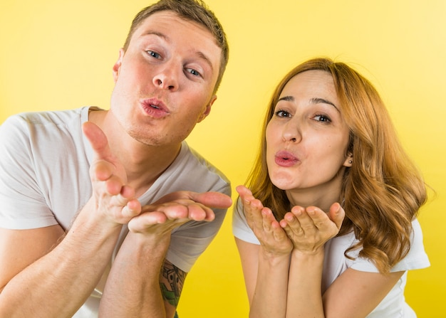 Jong paar blazende kussen voor camera tegen gele achtergrond