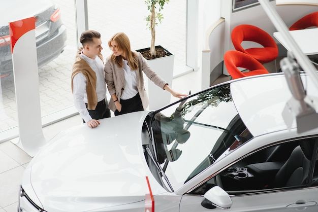Jong paar dat bij autoshowroom glimlacht
