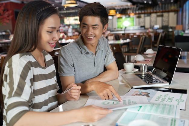 Jong paar dat details van levensverzekeringspolis bestudeert