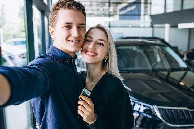 Jong paar dat een auto in een autotoonzaal omzeilt