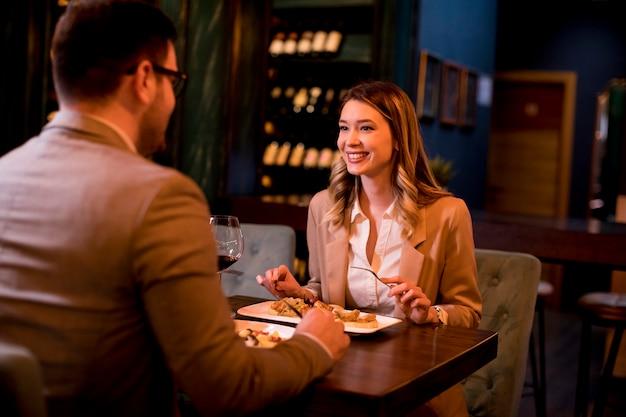 Jong paar dat een diner in het restaurant heeft en rode wijn drinkt