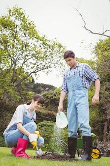 Jong paar dat een jong boompje in tuin water geeft