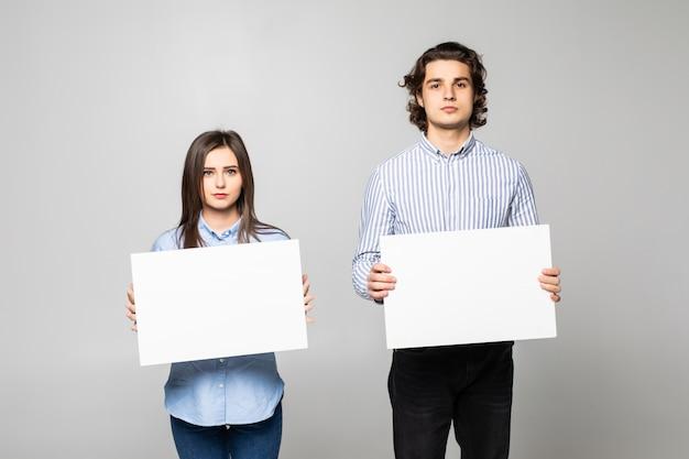 Jong paar dat een lege affiche geïsoleerd houdt