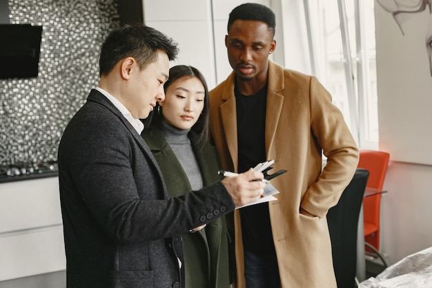 Jong paar dat een nieuw huis koopt. aziatische vrouw en afrikaanse man. documenten ondertekenen bij nieuw huis.
